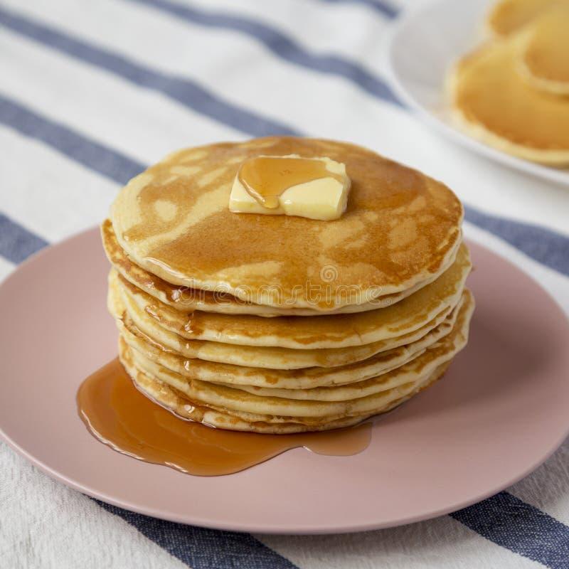 Bunt av hemlagade pannkakor med smör- och lönnsirap på en rosa platta, sikt för låg vinkel closeup arkivfoton
