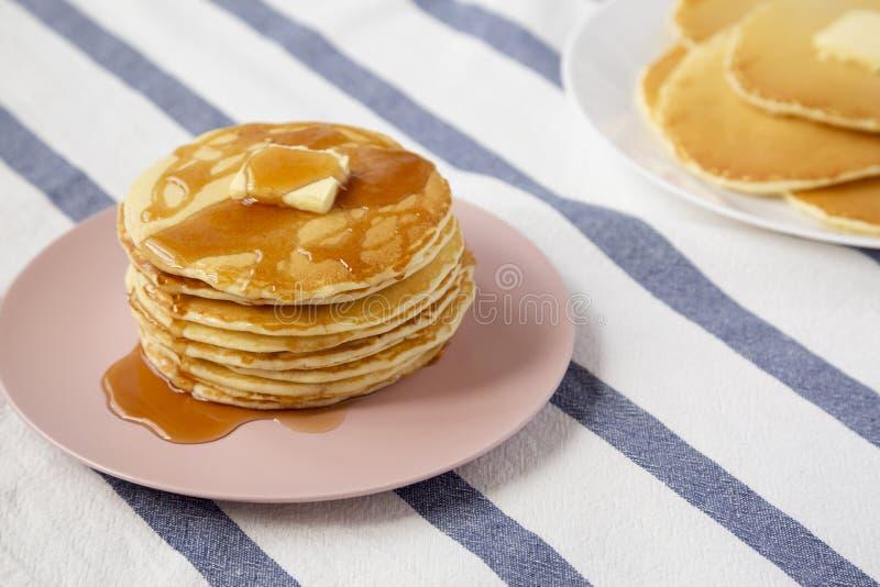 Bunt av hemlagade pannkakor med smör- och lönnsirap på en rosa platta, sikt för låg vinkel N?rbild royaltyfria bilder