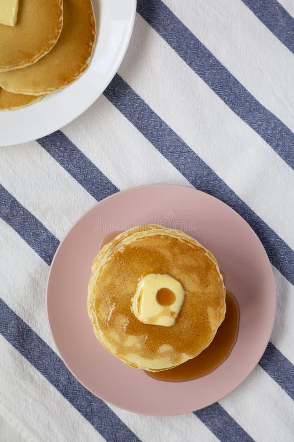 Bunt av hemlagade pannkakor med smör- och lönnsirap på en rosa platta, sikt från över Den b?sta sikten, ?ver huvudet som ?r plan  royaltyfri fotografi