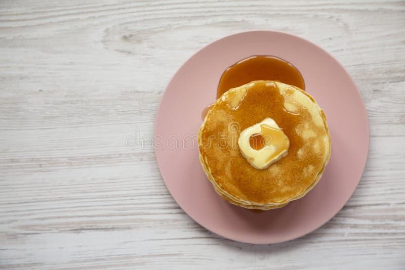 Bunt av hemlagade pannkakor med smör- och lönnsirap på en rosa platta på en vit träbakgrund, bästa sikt ?ver huvudet fr?n royaltyfri foto