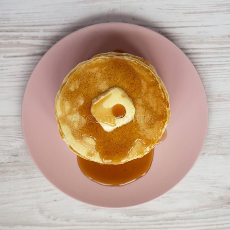 Bunt av hemlagade pannkakor med smör- och lönnsirap på en rosa platta på en vit träbakgrund, bästa sikt ?ver huvudet fr?n royaltyfria bilder