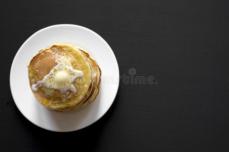 Bunt av hemlagade pannkakor med smör på den vita plattan över svart bakgrund, bästa sikt fotografering för bildbyråer