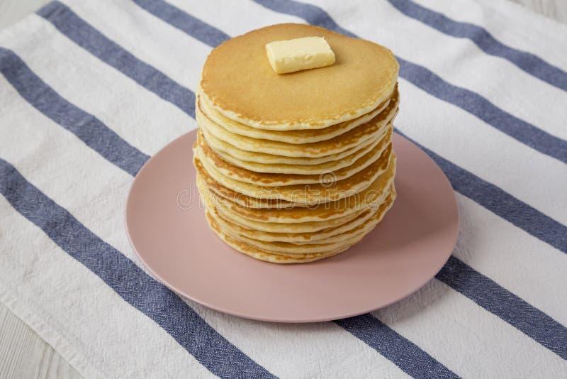Bunt av hemlagade pannkakor med smör på en rosa platta, sikt för låg vinkel N?rbild arkivbild
