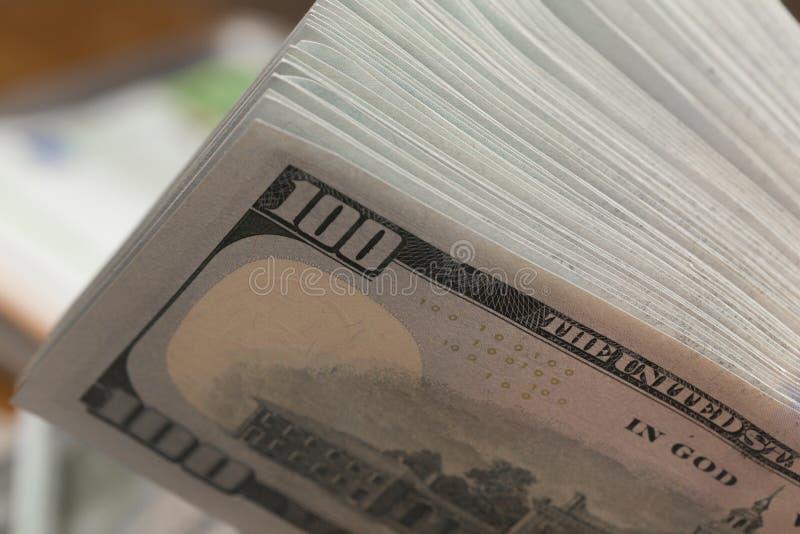 Bunt av hundra dollarräkningar på en trätabell royaltyfri fotografi