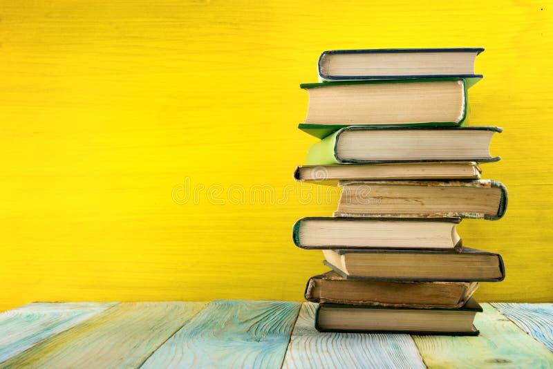 Bunt av inbunden bokböcker, dagbok på trädäcktabellen och gulingbakgrund tillbaka skola till kopiera avstånd Utbildning arkivfoto