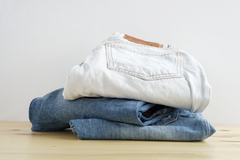 Bunt av jeans i olika färger på trätabelltextur arkivfoto
