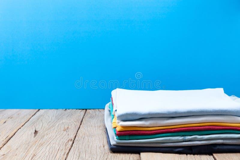 Bunt av kläder på träplankan, blå bakgrund arkivbild