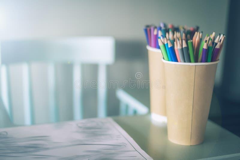 Bunt av kulöra blyertspennor i ett exponeringsglas på barns tabell, bredvid en hög stol, rätt, ett hemtrevligt ställe att dra för arkivfoton