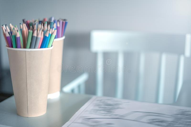 Bunt av kulöra blyertspennor i ett exponeringsglas på barns tabell, bredvid en hög stol som är vänster, ett hemtrevligt ställe so royaltyfri bild