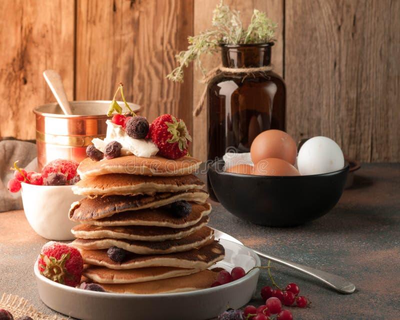 Bunt av läckra bruna traditionella amerikanska pannkakor med gräddfil och nya bär royaltyfri fotografi