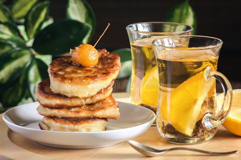Bunt av läckra pannkakor på den vita plattan med bär i sirap och honung och te med citronen för den sunda frukosten - hemlagad he royaltyfri fotografi