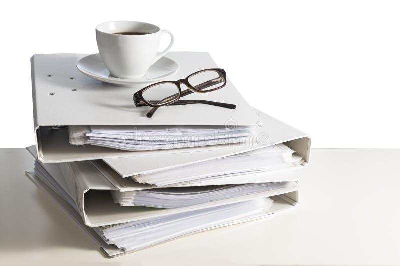 Bunt av mappar, exponeringsglas och en kopp kaffe på ett skrivbord, isolat royaltyfria bilder