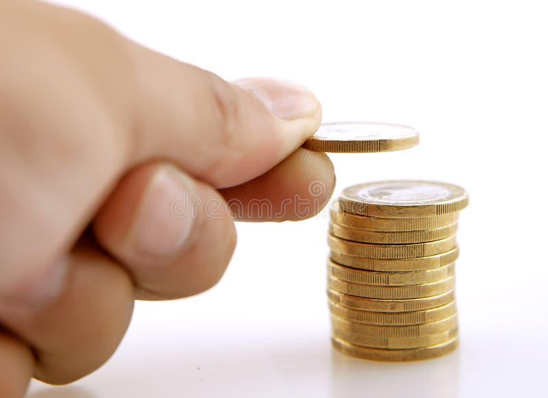 Bunt av mynt med en hand som mer tillfogar ett mynt royaltyfri foto