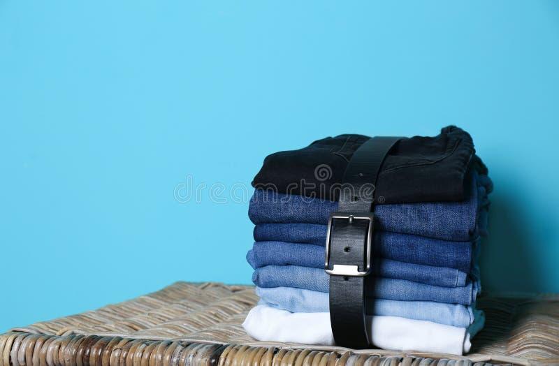 Bunt av olik jeans på korg mot färgväggen royaltyfri fotografi