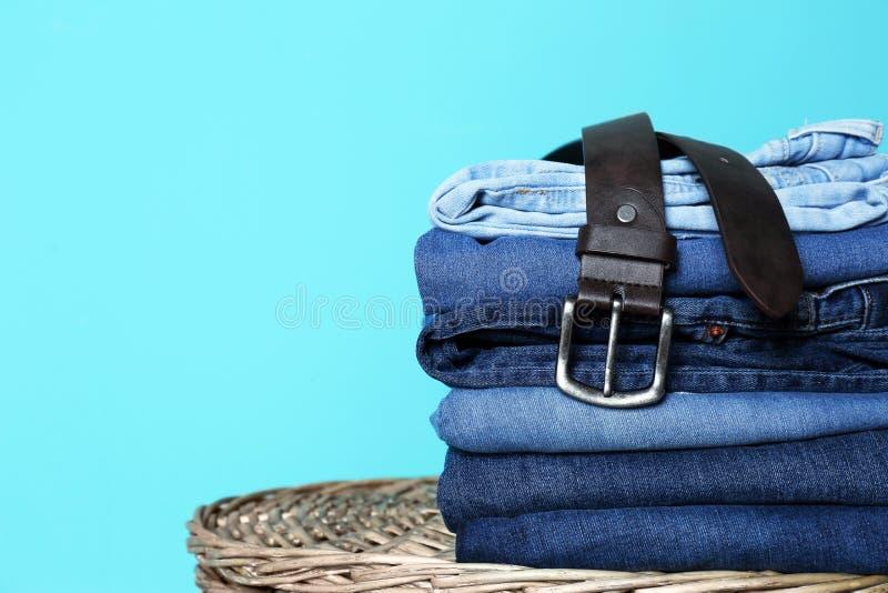 Bunt av olik jeans på korg mot färgväggen med utrymme royaltyfria foton