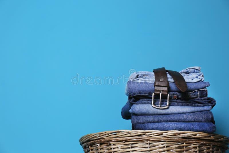 Bunt av olik jeans på korg mot färgväggen med utrymme royaltyfri fotografi