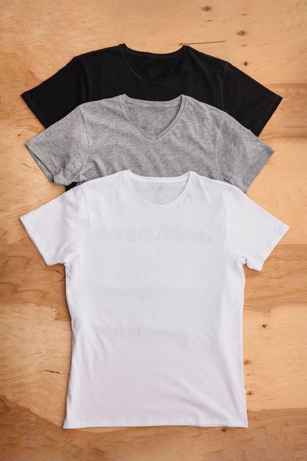 Bunt av olika färgade mäns T-tröja på träbakgrund arkivbild