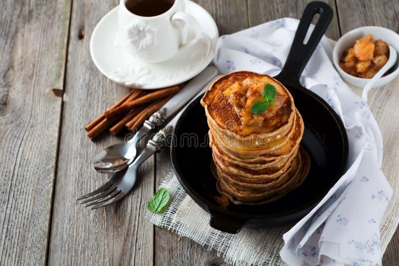 Bunt av pannkakor från bovetemjöl med bakad äpplen och kanel på gammal träbakgrund sund frukost royaltyfria bilder