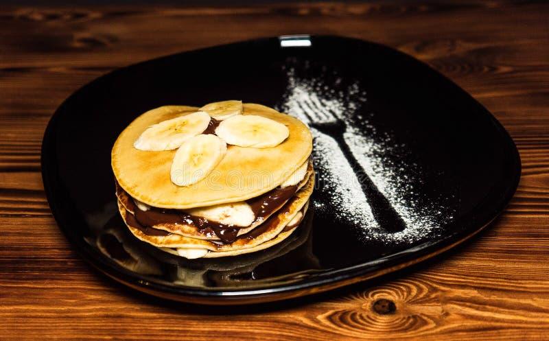 Bunt av pannkakor med bananskivor och chokladsirap på en platta royaltyfri fotografi