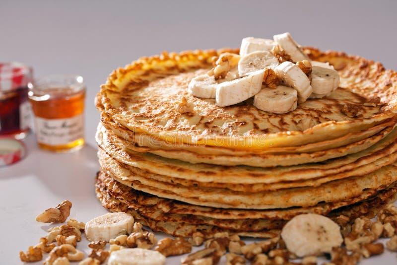 Bunt av pannkakor med frukter, muttrar och honung. royaltyfri foto