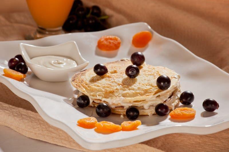 Bunt av pannkakor med frukter, muttrar och honung. royaltyfri bild