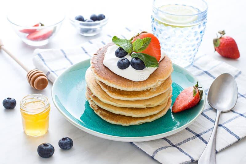 Bunt av pannkakor på plätera Morgonfrukost med bär på tabellen royaltyfri bild