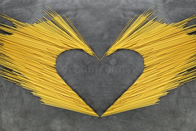 Bunt av rå gul lång spagetti på en gammal träbakgrund kopiera avstånd royaltyfri fotografi