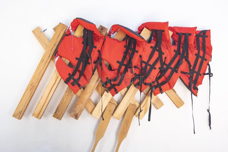 Bunt av röda flytvästar som hänger på beställnings- trähängare arkivbild