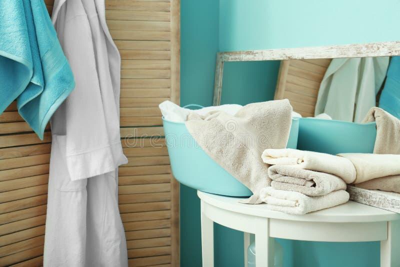 Bunt av rena handdukar och tvättkorgen royaltyfri foto