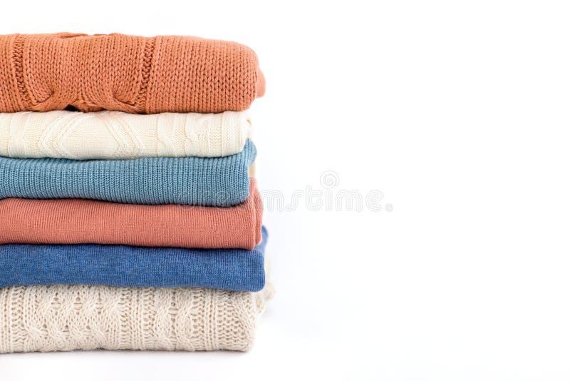 Bunt av varma pastellfärgade tröjor för apelsin och för blått på vit arkivfoto