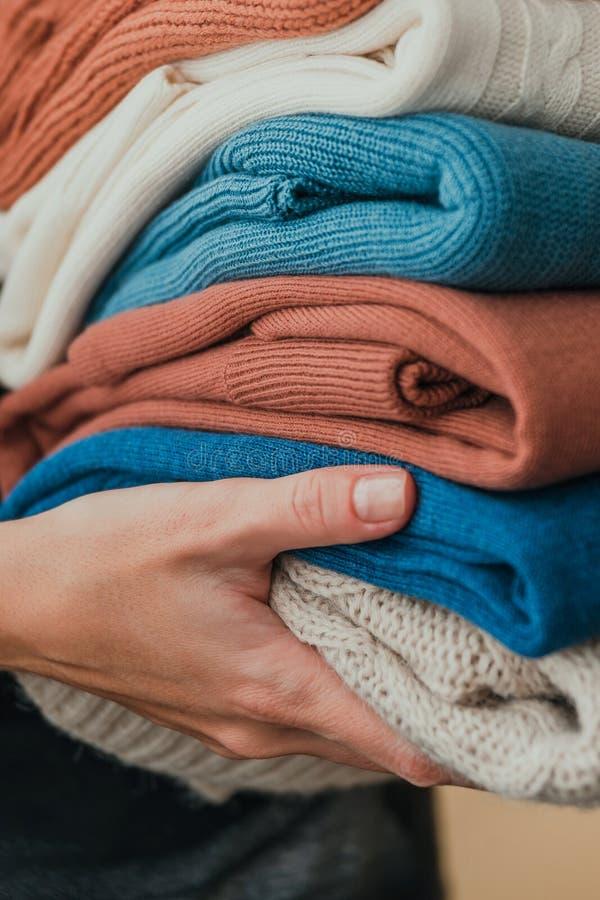 Bunt av varma pastellfärgade tröjor för apelsin som och för blått rymmer i händer royaltyfria foton
