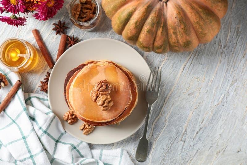 Bunt av varma smakliga pumpapannkakor med honung och valnötter på plattan arkivbild
