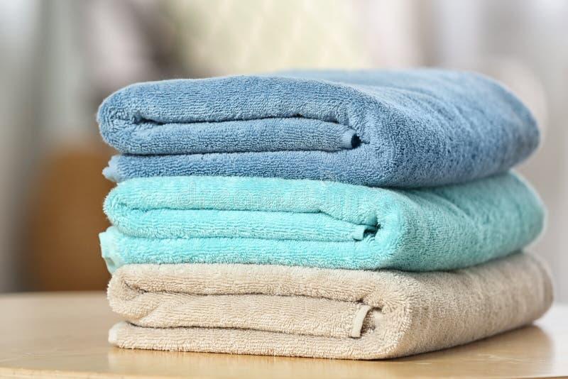 Bunt av vikta rena mjuka handdukar på tabellen inomhus royaltyfria foton