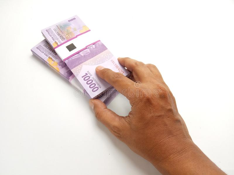 Bunt för hand för begreppsmässig bästa sikt erbjudande pengar för 10000 Rupiah Indonesien papper på vit bakgrund royaltyfri bild