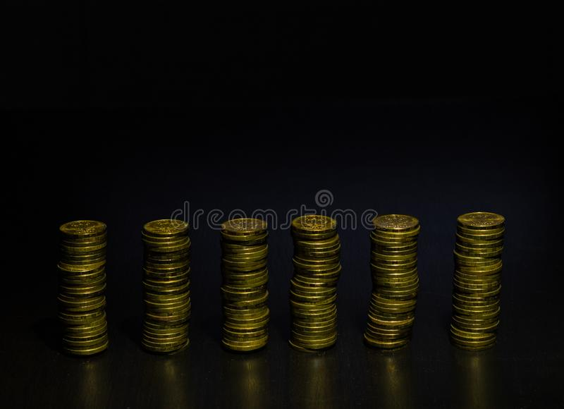 Bunt f?r guld- mynt Buntar av guld- mynt av j?mb?rdiga h?jder Diagram f?r vertikal st?ng arkivfoto
