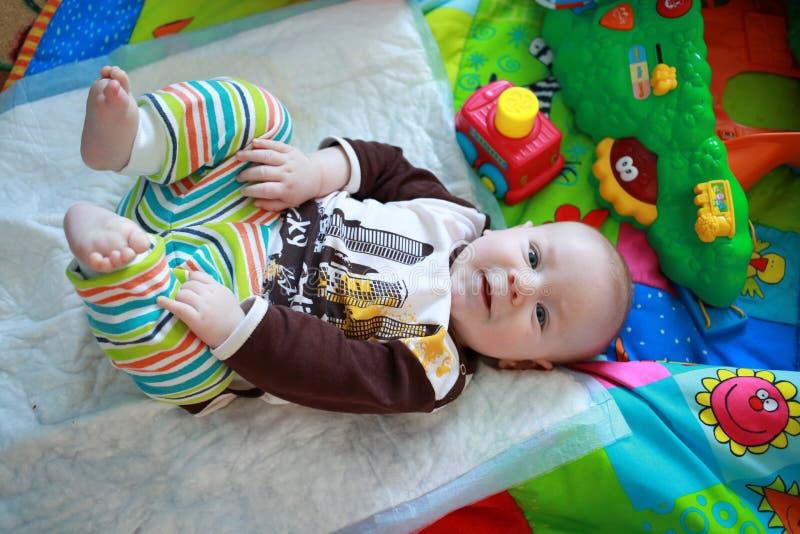 Bunt gekleideter kleiner Junge, der mit seinen Beinen spielt stockfotos