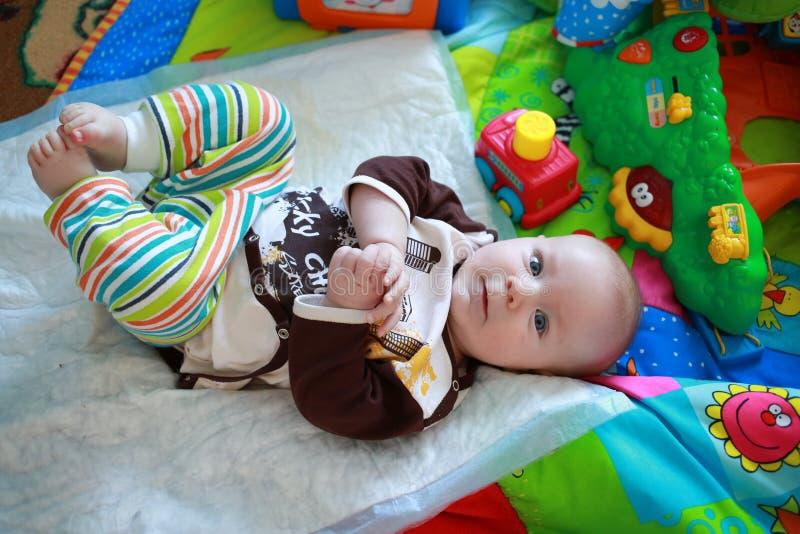 Bunt gekleideter kleiner Junge, der mit seinen Beinen spielt lizenzfreie stockbilder
