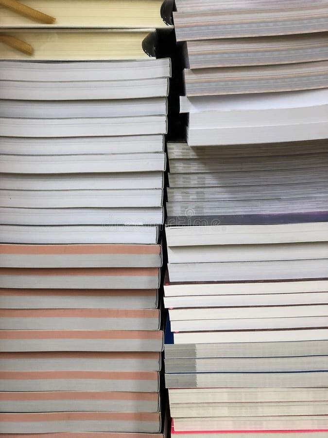 Buntar av böcker på hylla arkivfoton