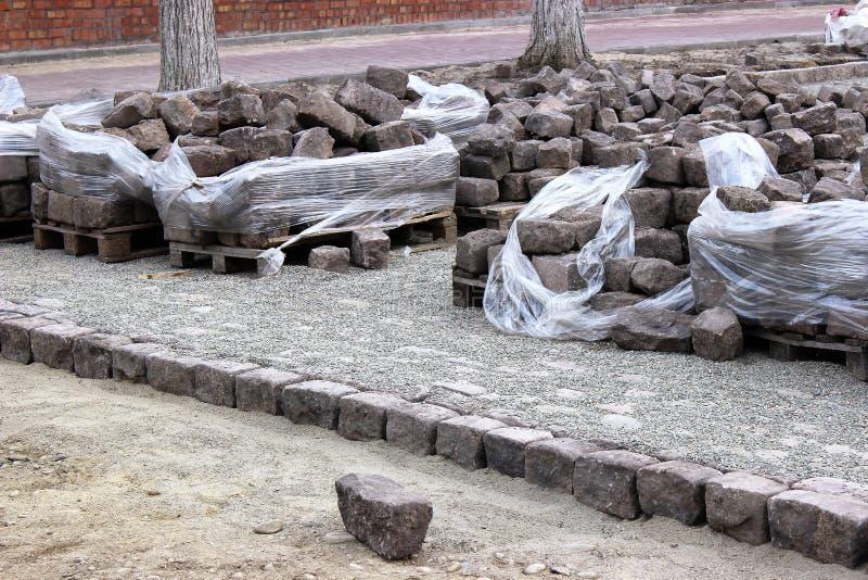 Buntar av gamla kullersten ligger längs gatan, som renoveras royaltyfria foton