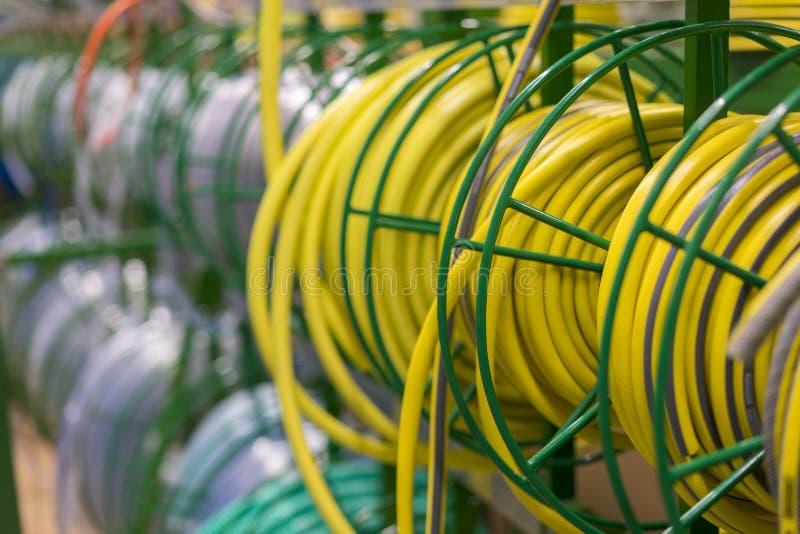 buntar av r?ret f?r pvc f?r rullar det gula plast- p? r?knaren i lagret Sale vattnar med slang i tr?dg?rden av olika producenter, royaltyfri foto