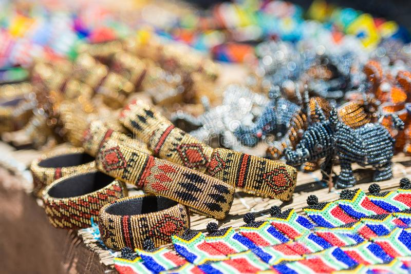 Bunte afrikanische Armbänder bördeln Kunst mit hellen unscharfen Farben des gelben Rosas und des Türkises im Hintergrund lizenzfreies stockbild