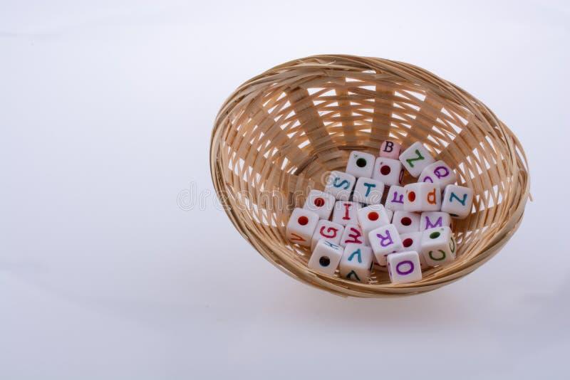 Bunte Alphabetbuchstabewürfel in einem Korb lizenzfreie stockbilder