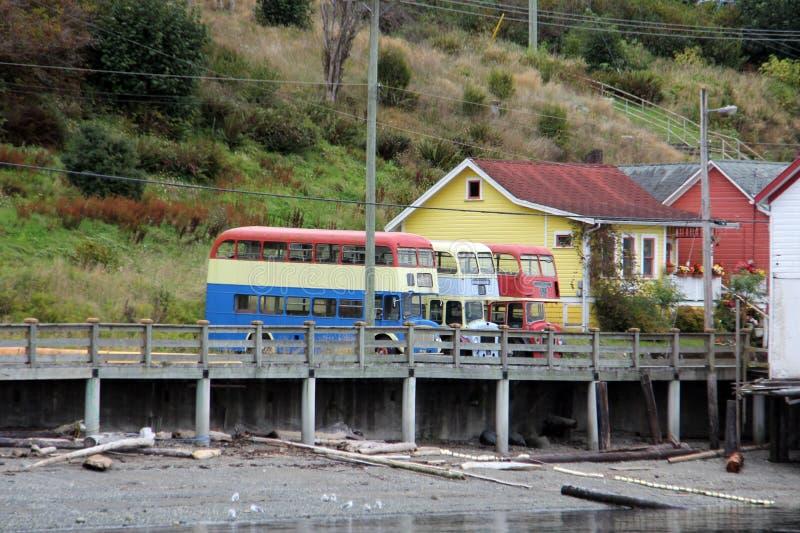 Bunte alte Doppeldeckerbusse und -gebäude alarmieren Bucht, BC lizenzfreies stockbild