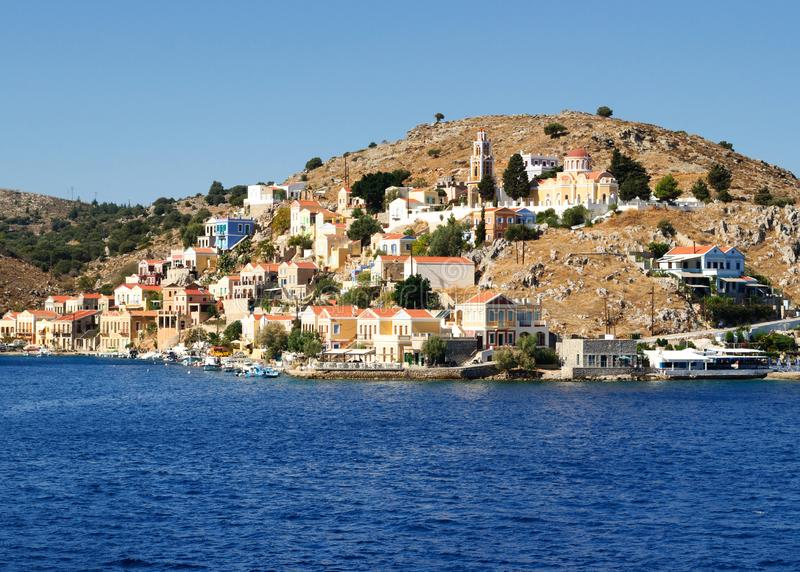 Bunte Architektur der Gebäude des felsigen Ufers der Insel Symi lizenzfreies stockfoto