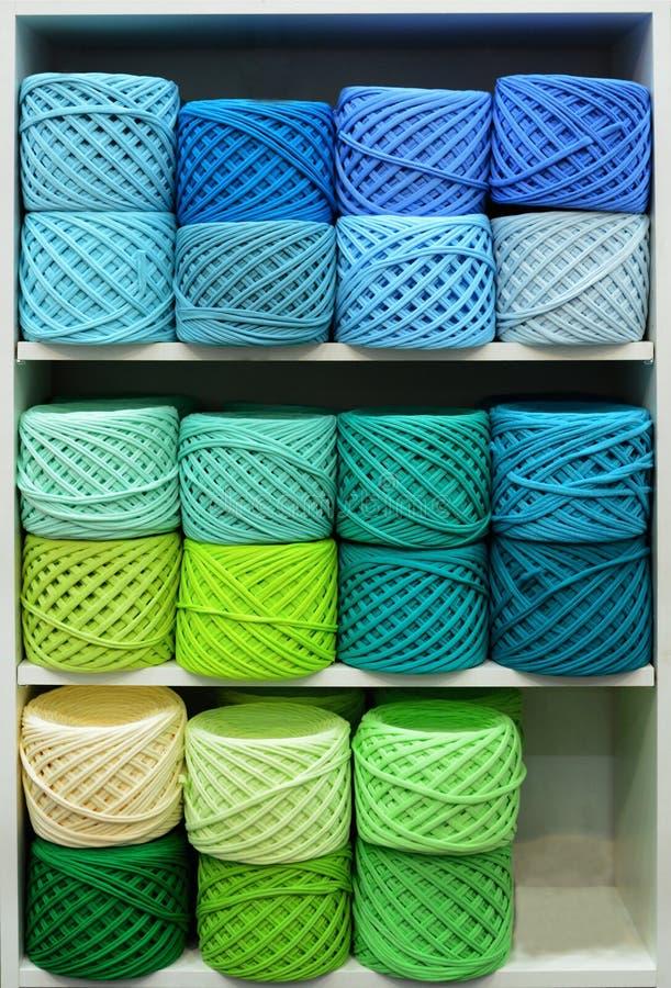 Bunte Bälle der Wolle auf Regalen Vielzahl von Strickgarnen Verschiedene Garnbälle in den mehrfachen Farben lizenzfreie stockfotos