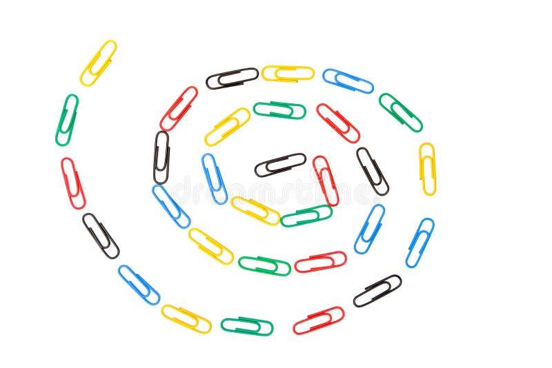Bunte Büroklammern in der Spirale im weißen Hintergrund stockfotos