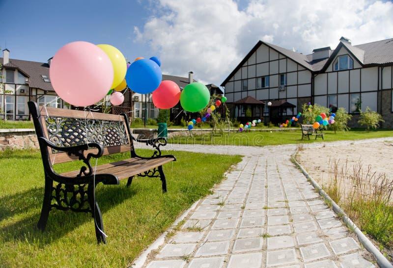 Bunte Ballone nähern sich brench auf Gasse und Häusern lizenzfreie stockfotografie