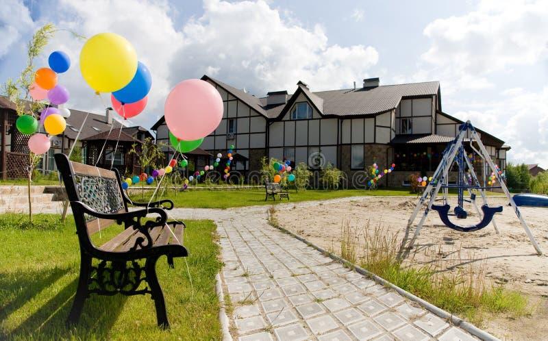 Bunte Ballone nahe Bank auf Gasse mit Schwingen lizenzfreie stockfotos