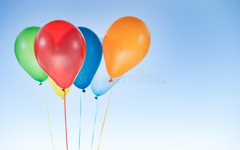Bunte Ballons zum Geburtstag und Feiern am blauen Himmel isoliert lizenzfreie stockbilder