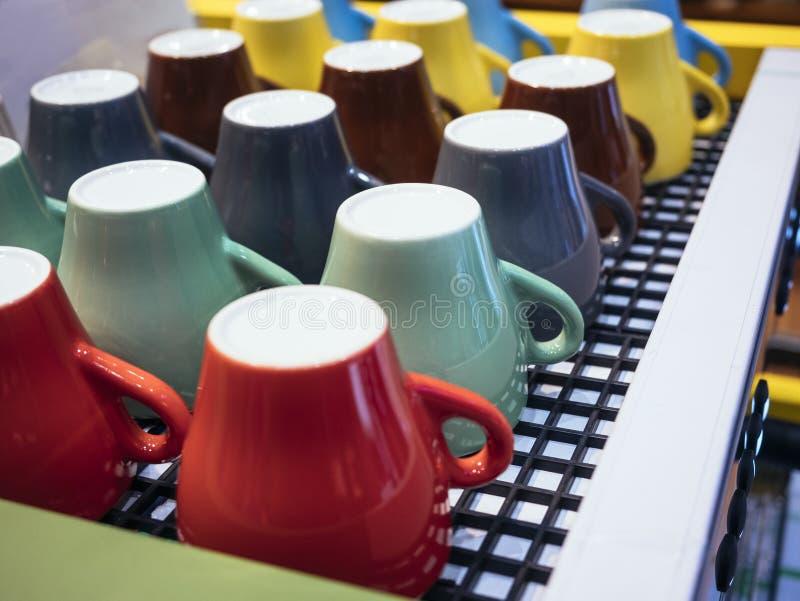 Bunte Becher auf Kaffee-Maschinen-Café-Restaurant lizenzfreie stockbilder